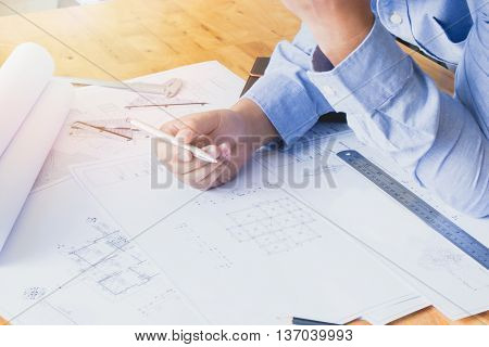 Architects Working With Blueprints In The Office