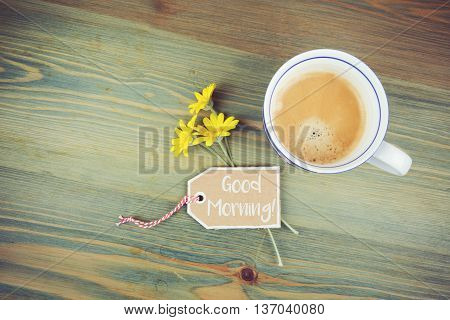 Coffee cup and daisy flowers with wish cardboard label on wooden table. Godd morning romantic message. View from above