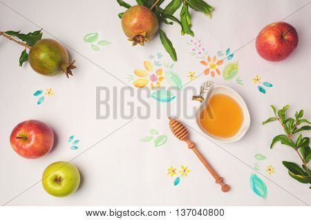 Honey apples and pomegranate on paper background with watercolor flowers. Jewish holiday Rosh Hashanah celebration concept.