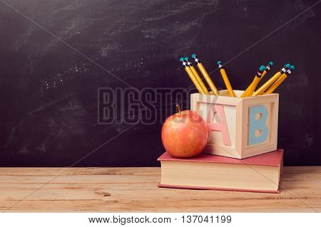 Back to school background with book apple and pencils on wooden table over chalkboard
