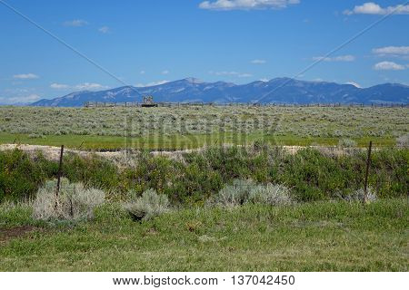 Sagebrush grazing land, a corral and mountains in the distance create a scenic view near Dillon, Montana.