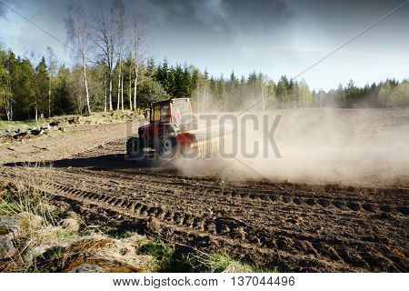 small farming tractor plowing a field, smoke of grain and mist