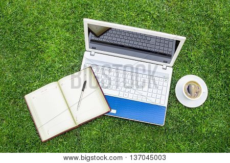 White Laptop notebook coffe cup and pen Placed On Green Grass Field.