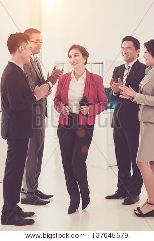 Coworkers clapping to pretty successful business lady