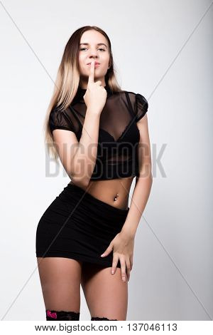young fashion woman in high heels, studio shot. woman in a short black skirt and a transparent top put her finger to her lips.