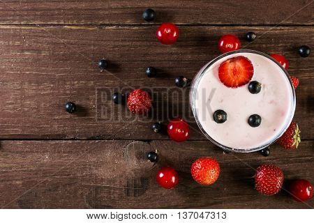 glass of berry yogurt smoothie with fresh ripe berries around on wooden table. top view