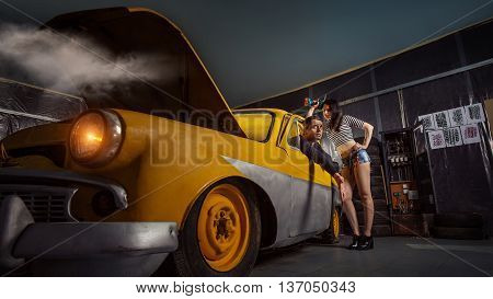 Woman Mechanic In Sexy Shirts Is Listening To The Complains Of The Owner Of An An Old Car.