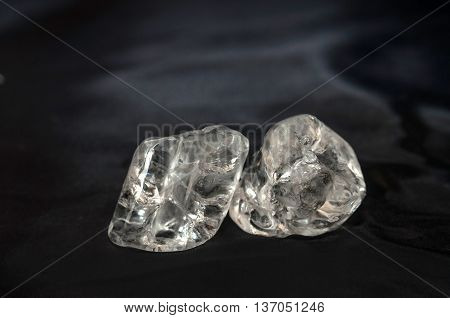 Two ice cubes laying on black silk fabric