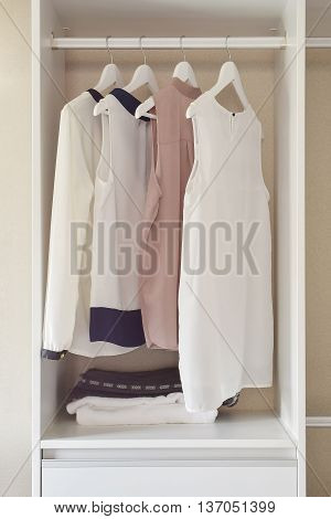 Row Of Dress Hanging On Coat Hanger In White Wardrobe