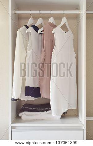 Row Of Dress Hanging On Coat Hanger In White Wardrobe