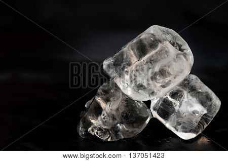 Three ice cubs laying on black pices of silk fabric