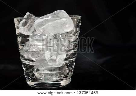 Glass of water with ice cube over a black background
