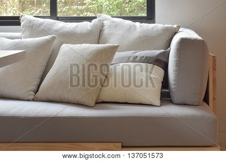 Beige varies size pillows setting on light gray comfy sofa