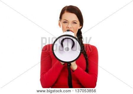 Young angry woman screaming through a megaphone