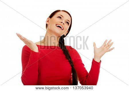 Happy young woman trying to catch something falling from the sky