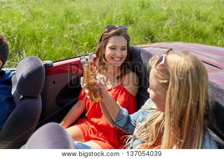leisure, road trip, travel, summer holidays and people concept - happy friends driving in cabriolet car along country road and drinking beer