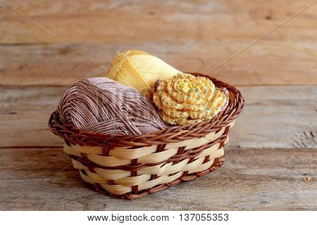 Yellow crochet flower with brown leaves and beads, cotton yarn in wicker basket on old wooden background. Easy crochet flower pattern. Crafts for kids, women, beginners