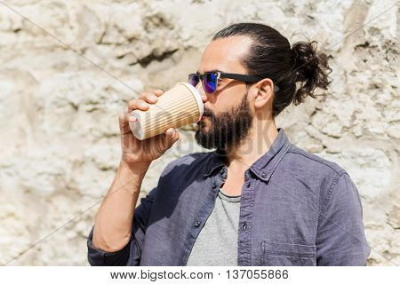 people, drinks, leisure and lifestyle - man drinking coffee from disposable paper cup on city street