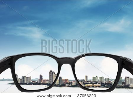 Glasses with city and sky with clouds background