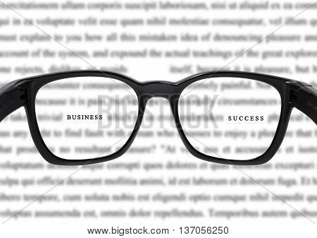 Glasses with blurred vocabulary, and focus on business and success word, concept of success