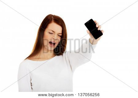 Young screaming woman shows broken touch screen mobile phone