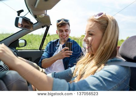 leisure, road trip, travel, summer holidays and people concept - happy couple driving in cabriolet car and taking picture by smartphone