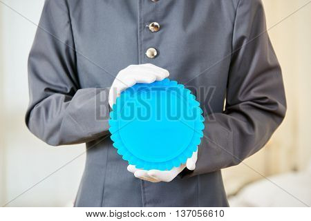 Hotel page holding blank blue badge in his hands