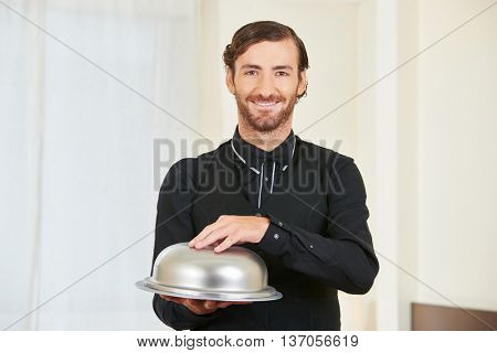 Smiling hotel clerk serving food with cloche on a tablet