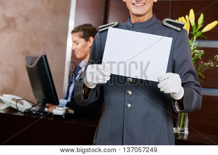 Page in hotel holding empty white blank sign in his hands