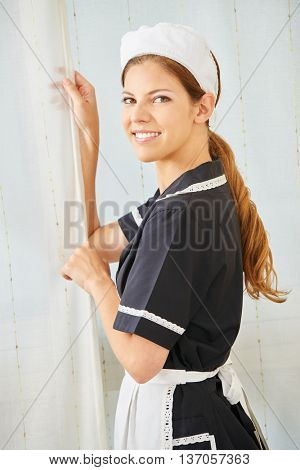 Smiling maid in uniform in a hotel room during housekeeping