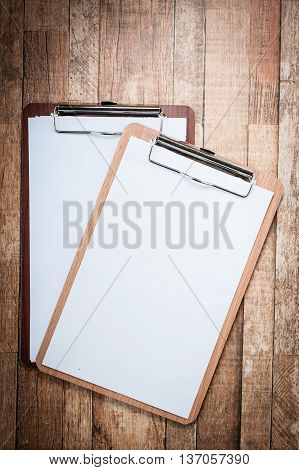 Clipboard with blank paper on wooden background.Vintage feel.