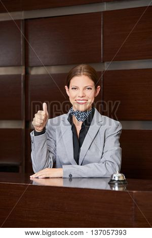 Smiling female hotel receptionist holding her thumbs up