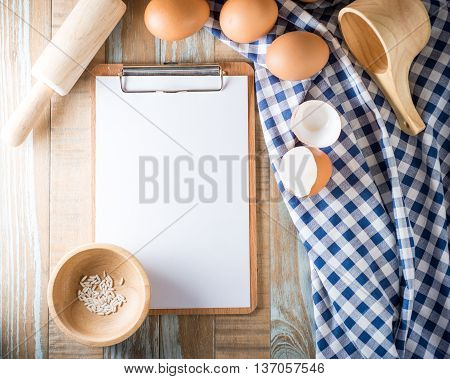 Blank clipboard with eggs on wooden background