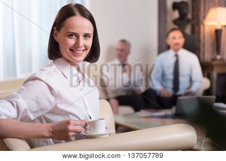 Enjoy best beverage, Cheerful delighted beautiful woman holding cup and drinking coffee while her colleagues sitting on the couch in the background