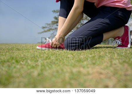 young Asian woman tying shoelace,park, shoe, lady