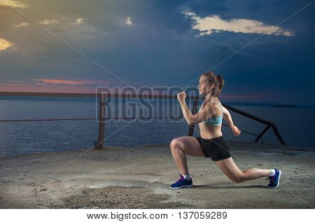 Fitness workout outdoors: fit caucasian woman doing lunges on sea pier