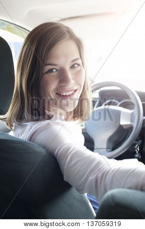 Cute caucasian woman indoor car holding steering wheel and turning to back seat