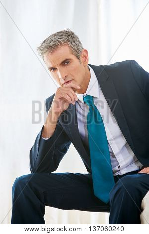 Pensive business man sitting thoughful in a hotel room