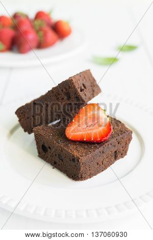 Close up of chocolate brownie cakes topped with strawberries and arranged on white plate