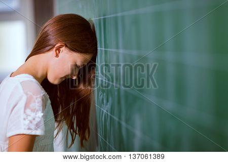 Little girl leaned her head on the blackboard