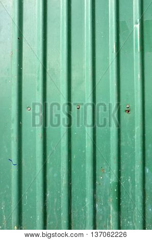 Texture of green corrugated metal with bolts