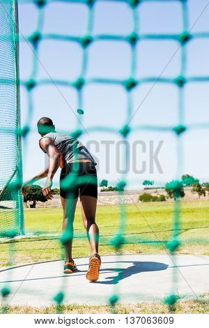 Rear view of athlete throwing discus in stadium during competition