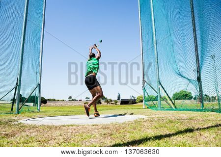 Rear view of athlete performing a hammer throw in stadium