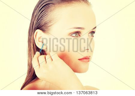 Woman cleans her ear