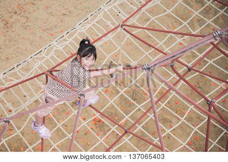 Beautiful asian girl climbing rope at playground
