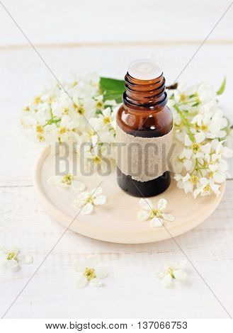 Floral refreshing aromatherapy. Bottle of cosmetic aroma oil and blossom.