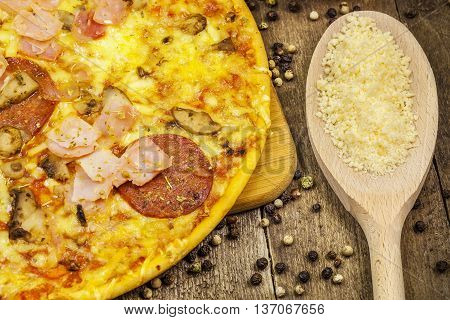 Pizza with cheese, bacon and salami on wooden table