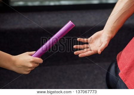 Athlete passing a baton to the partner at gym