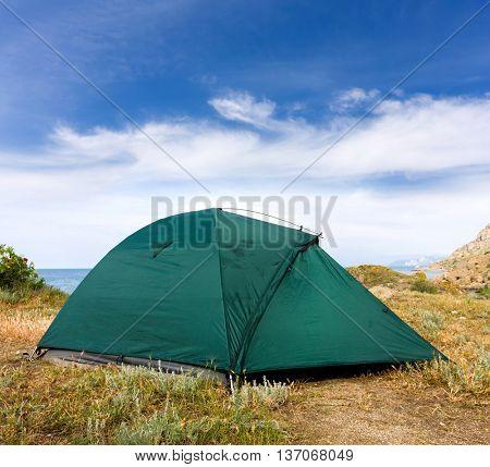 modern tourist tent on meadow near sea