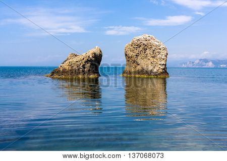 summer scene with two rocks in sea water